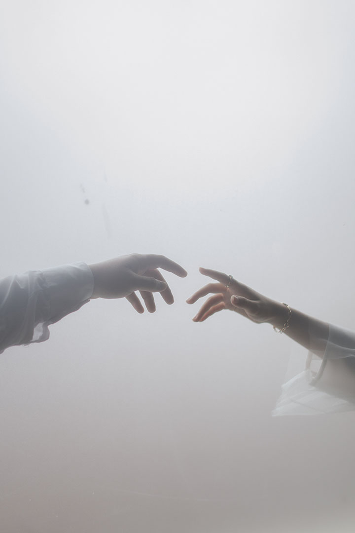 two people almost touching their fingers
